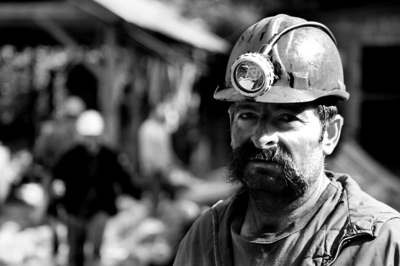 black and white photo of coal miner with mustach and mining helmet on